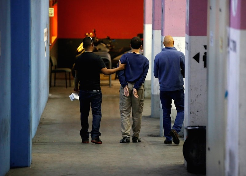 Israeli teen (C) arrested in Israel on suspicion of making bomb threats against Jewish community centres in the United States, Australia and New Zealand over the past three months. (Reuters Photo)
