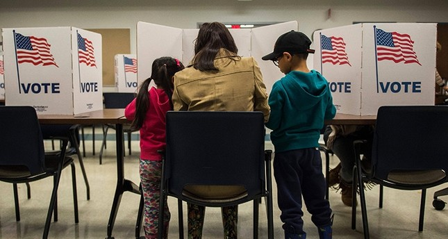 A woman and her children vote at a polling station during the mid-term elections at the Fairfax County bus garage in Lorton, Virginia on Nov. 6, 2018. (AFP Photo)