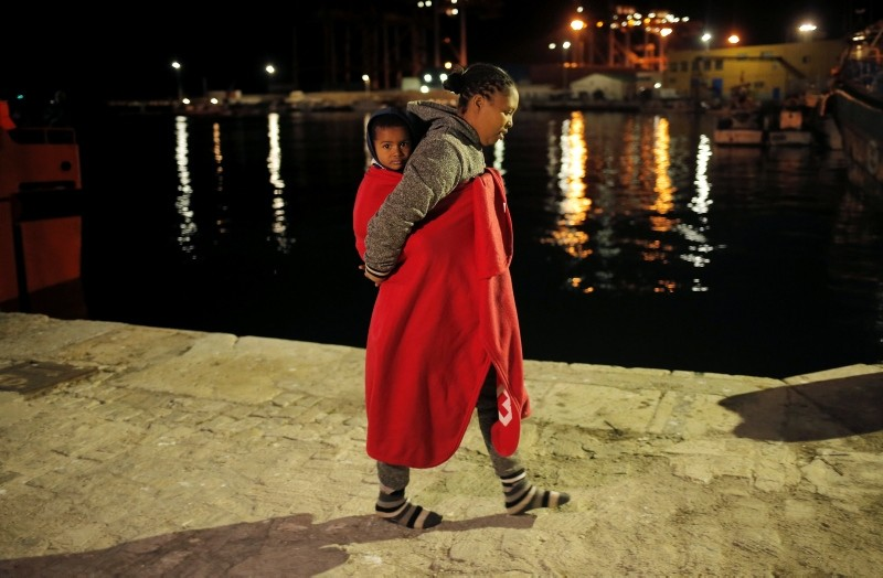 A migrant woman carries a child, intercepted off the coast in the Mediterranean Sea, after disembarking a rescue boat at a port on Christmas Eve in Malaga, southern Spain, December 24, 2018. Picture taken December 24, 2018. (Reuters Photo)
