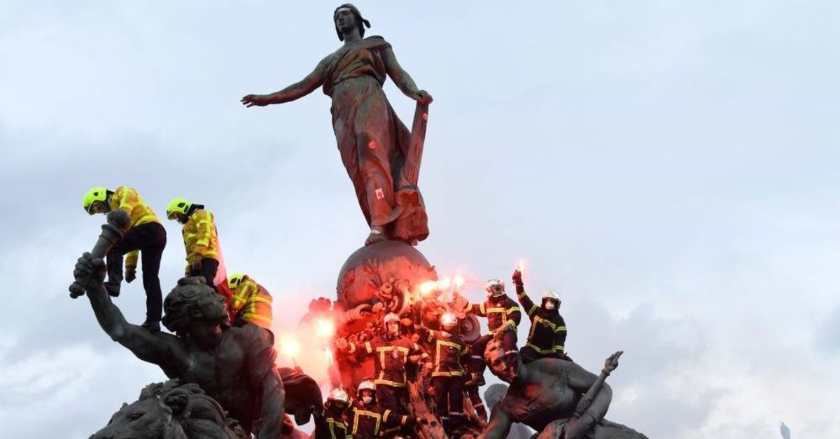 Firefighters brandish flares as they climb on the Statue of Republic Triumph at Nation Square during a demonstration to protest against French government's plan to overhaul the country's retirement system in Paris, Jan. 28, 2020. (AFP Photo)