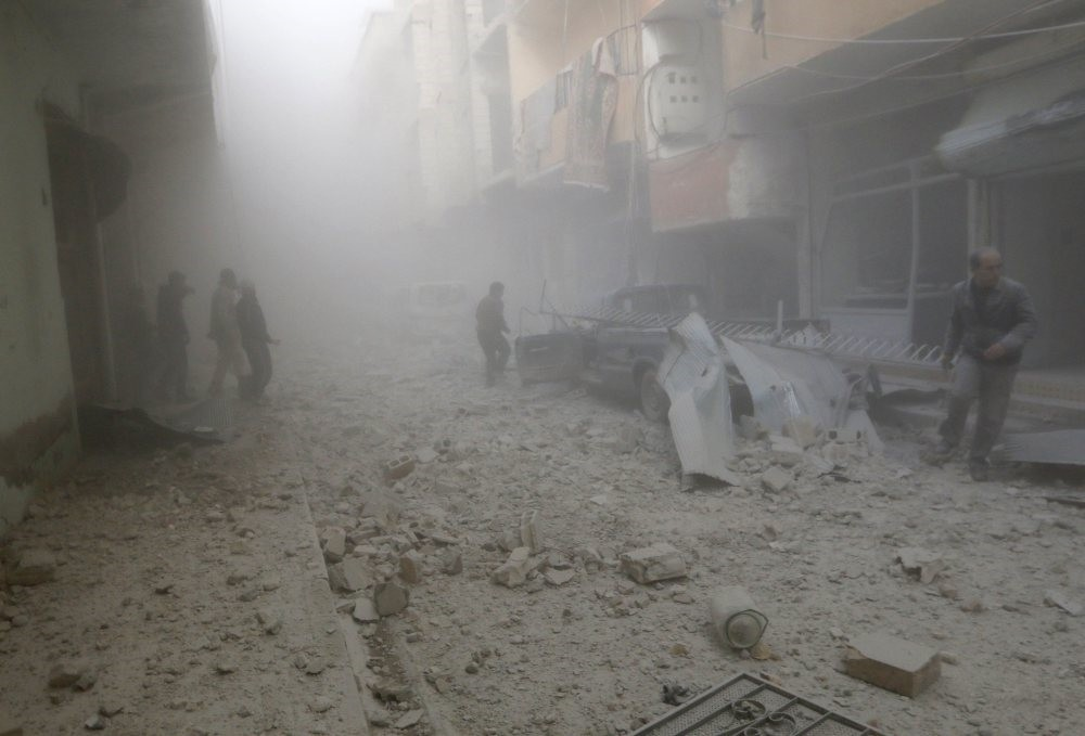 People walking on rubble as they inspect a site in Raqqa, eastern Syria, hit by the airstrikes of forces loyal to the Assad regime, Nov. 27, 2014.