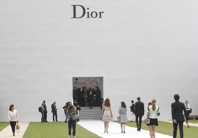 Guests arrive to attend Dior's Fall-Winter 2014-2015 Haute Couture fashion collection in Paris. Magnate behind LVMH luxury empire seeks to strengthen control over Christian Dior in a multibillion-dollar deal combining fashion industry heavyweights.