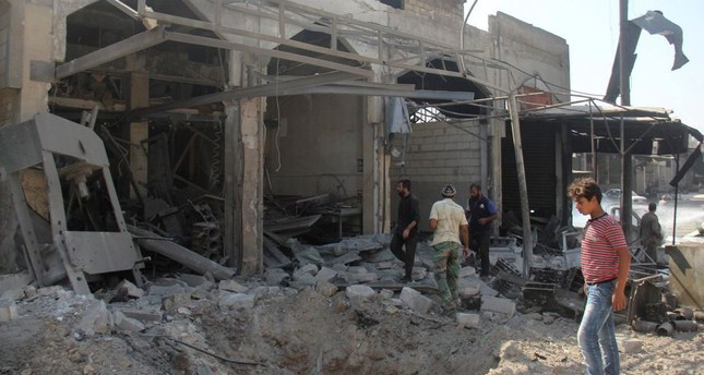 People inspect a damaged building in Idlib after warplanes pounded the city yesterday.
