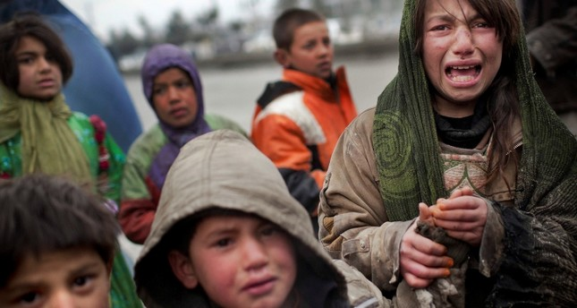 An Afghan refugee girl reacts after another child stole her food voucher while she was queuing in front a truck organized by the World Food Program in Kabul, Sunday, March 4, 2012. (AP Photo)