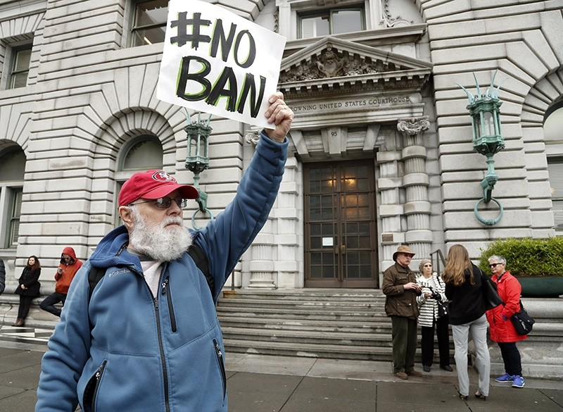 An anti-travel ban protestor with a poster reading 'NO BAN' stands outside the Ninth US Circuit Court of Appeals (EPA Photo)
