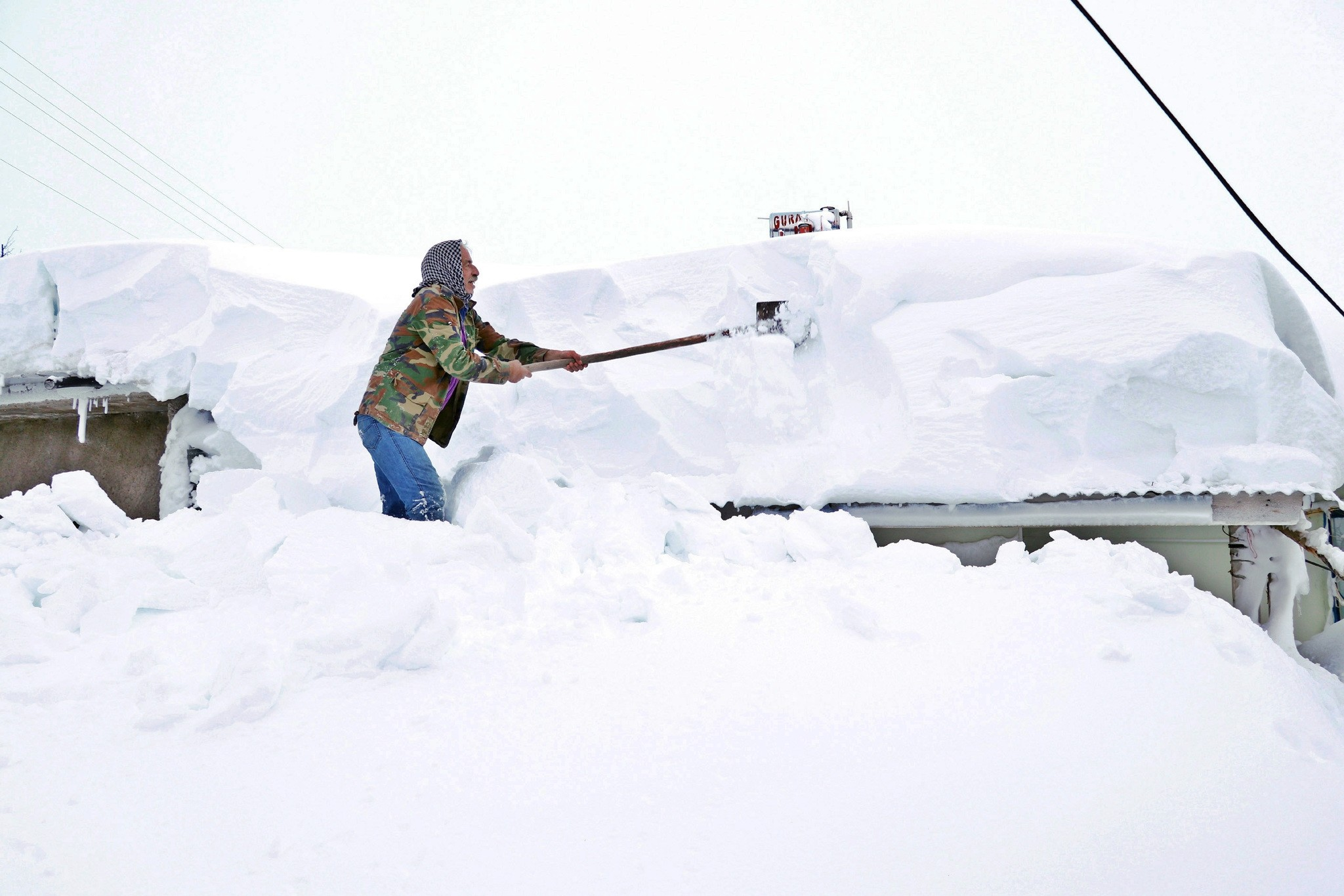 A man shovels snow from the roof of a house in the eastern city of Elazu0131u011f, Jan. 16, 2019.