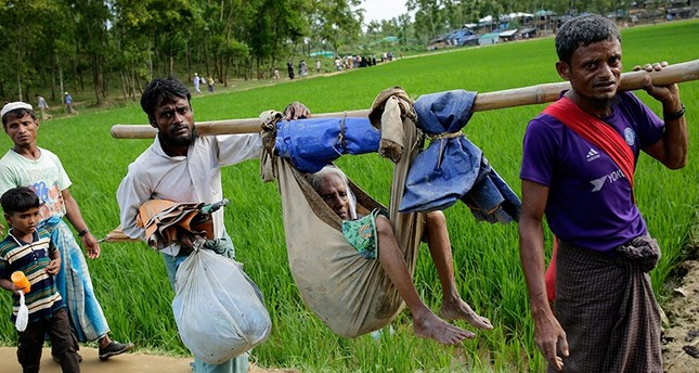 Two Rohingya men carry their mother in a hammock as they walk into a refugee camp in Ukhiya, Cox's Bazar, Bangladesh, Sept. 11, 2017. (EPA Photo)