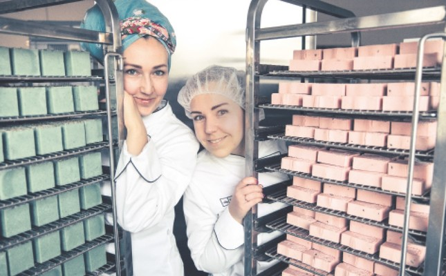 Ania (L) and Ula Bielun stand beside handmade soaps produced in their facility in the port city of Szczecin, the capital of the West Pomerania Province and the seventh largest city of Poland.