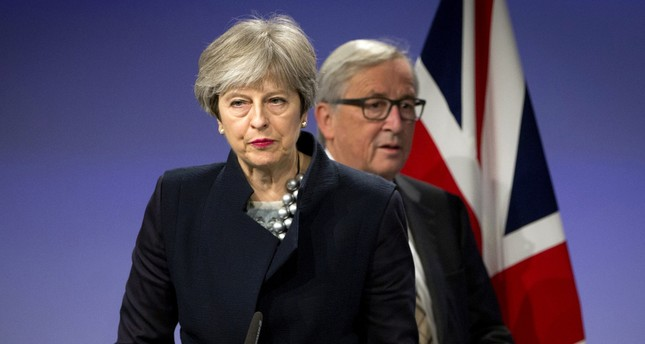 European Commission President Jean-Claude Juncker, right, walks behind British Prime Minister Theresa May prior to addressing a media conference at EU headquarters in Brussels on Monday, Dec. 4, 2017. (AP Photo)