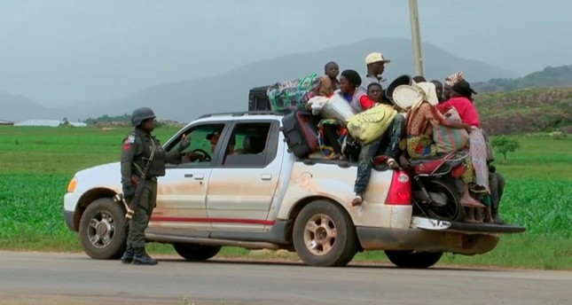 Security personal at a check point observe a pickup truck loaded with people and their belongings as they drive off to safety as police attempt to restore calm, in the town of Jos, Nigeria, Sunday June 25, 2018. (Nigeria Government via AP)