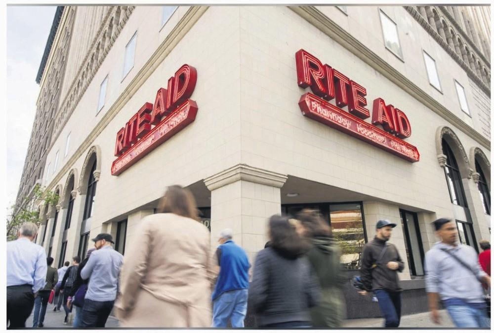 Pedestrians pass a Rite Aid store in Oakland, California, U.S., April 1, 2015.