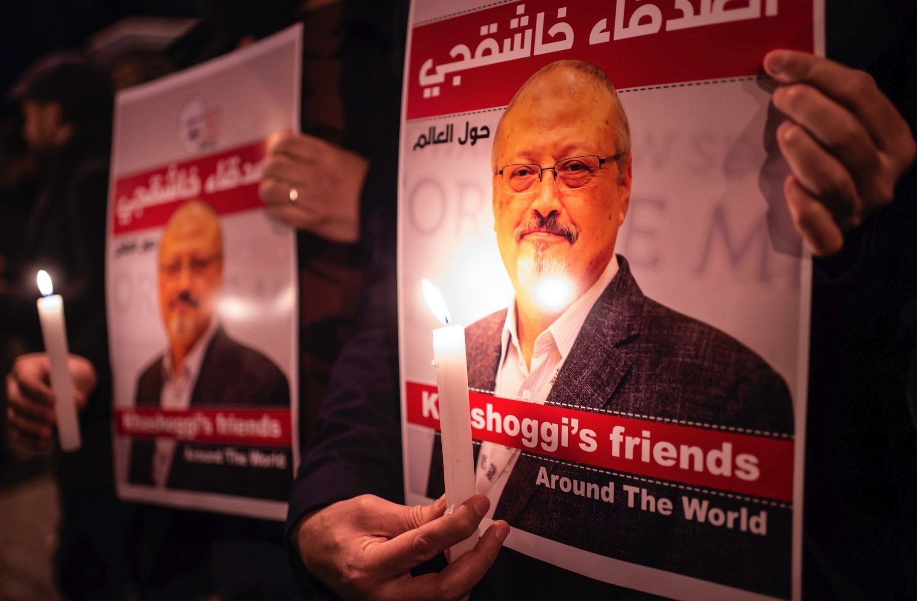 People hold posters at murdered Saudi journalist Jamal Khashoggi and light candles during a gathering outside the Saudi Arabia Consulate in Istanbul, Oct. 25, 2018.