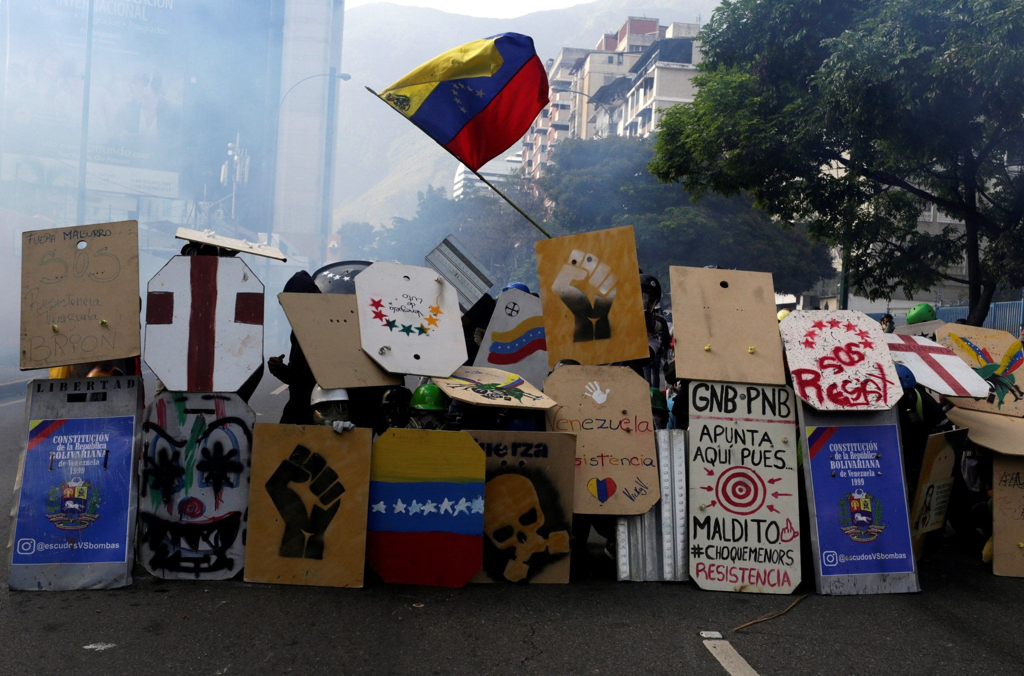 Opposition supporters use home made shields to protect themselves during a rally against President Nicolas Maduro in Caracas, Venezuela. (REUTERS Photo)