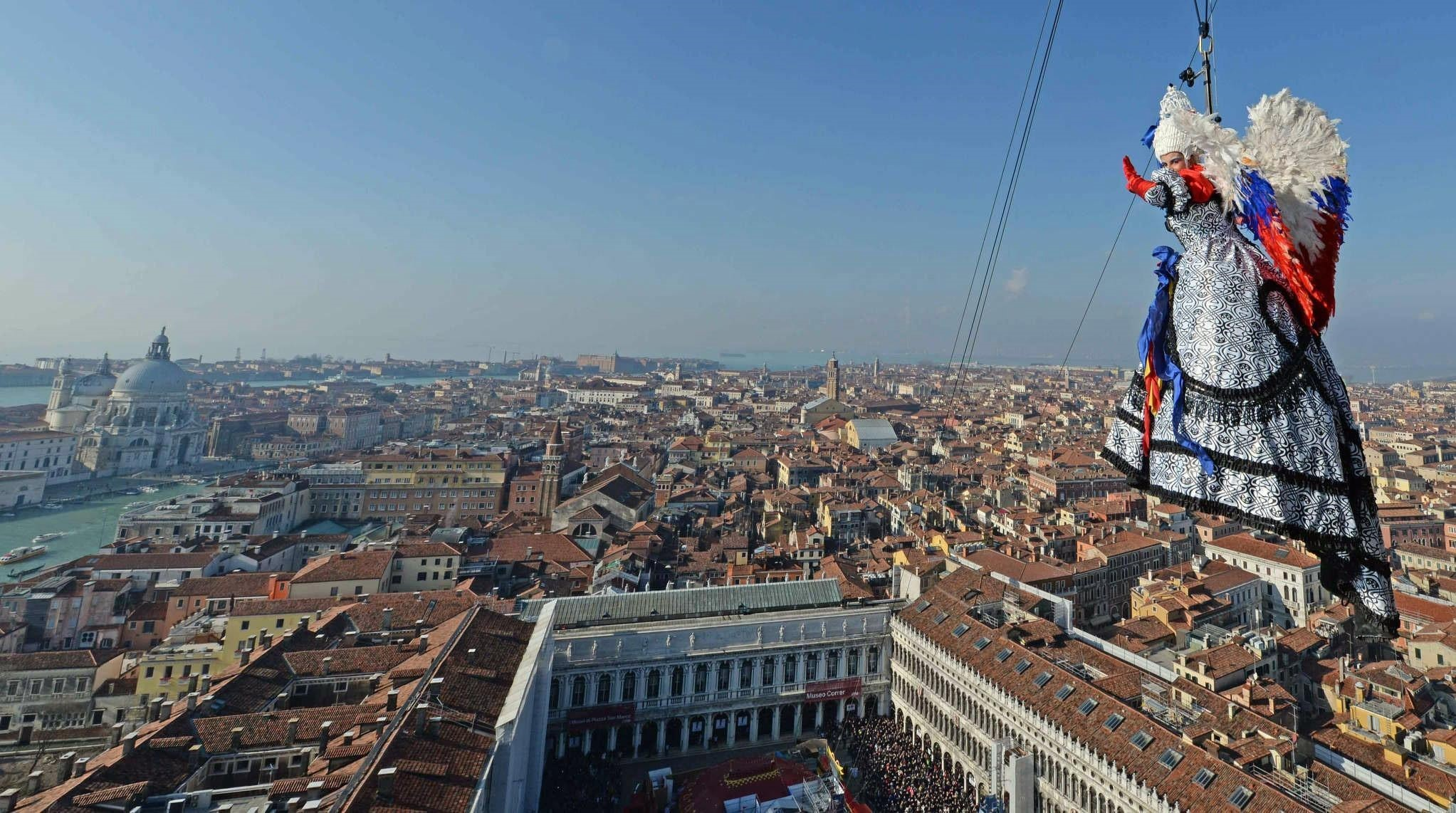 A handout photo shows Elisa Costantini, the winner of the 'Festa delle Marie' (Marie contest), descending on a zip line from the Campanile (Bell Tower) into the Piazza San Marco (EPA Photo)