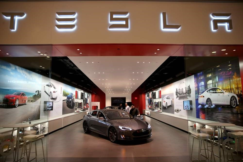 People look at a Tesla vehicle on the showroom floor at Dadeland Mall in Miami.