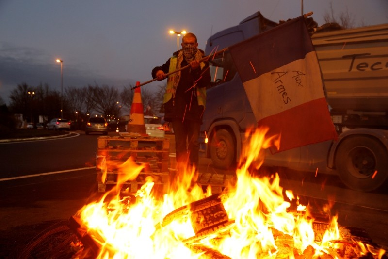 A protester wearing a yellow vest, the symbol of a French drivers' protest against higher diesel fuel prices, holds a flag with words ,To arms, near burning debris at the approach to the A2 Paris-Brussels Motorway, December 4, 2018. (Reuters Photo)