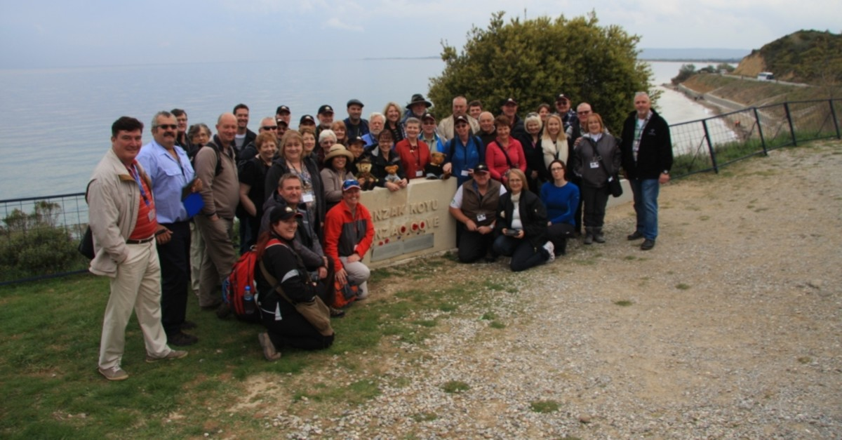 A tourist group led by Craig Roach, first from right, pose after visiting the Anzac Cove in Gallipoli.