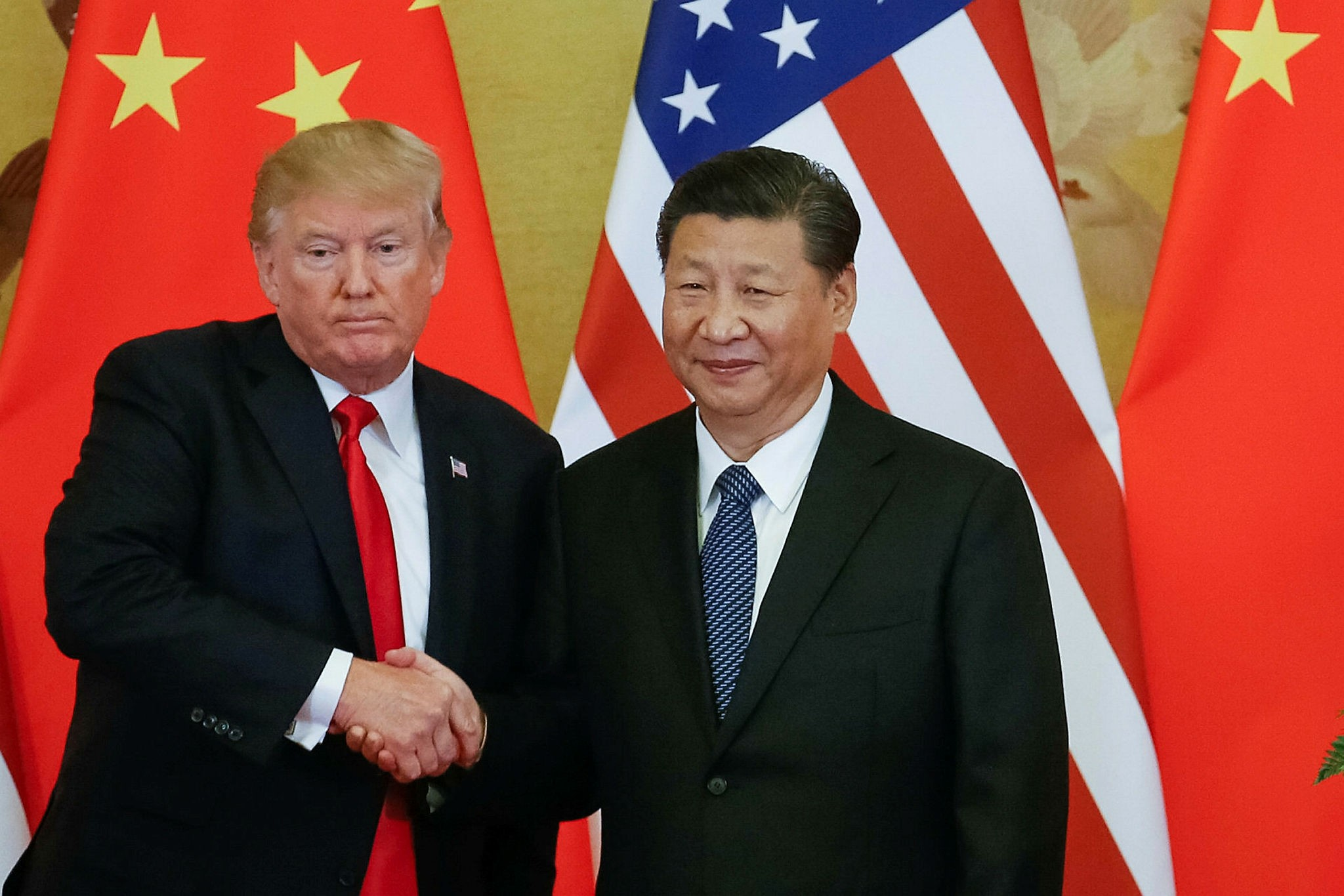 U.S. President Donald Trump (L) and Chinese President Xi Jinping (R) shake hands during a press conference, Beijing, Nov. 9.