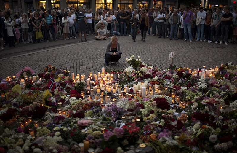People gather during a candle light vigil to pay tribute to victims of the twin attacks near the Domkirke church on Friday, in central Oslo, Norway, Saturday, July 23, 2011. (AP Photo)
