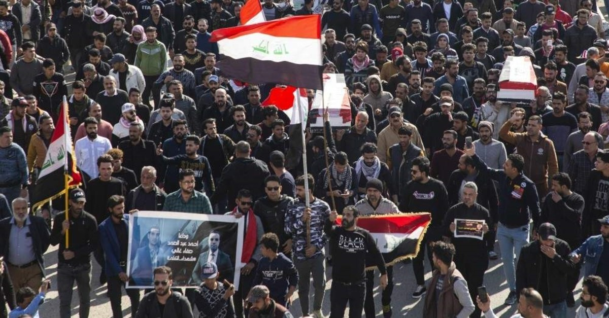 Iraqis carry mock coffins as they take part in a rally to mourn two reporters shot dead in the country's southern city of Basra, Jan. 11, 2020. (AFP Photo)