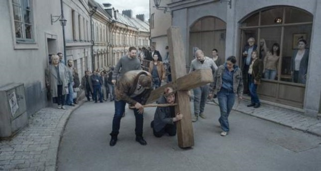 A scene from About Endlessness depicting the priest bearing a huge cross and being tortured by passersby.