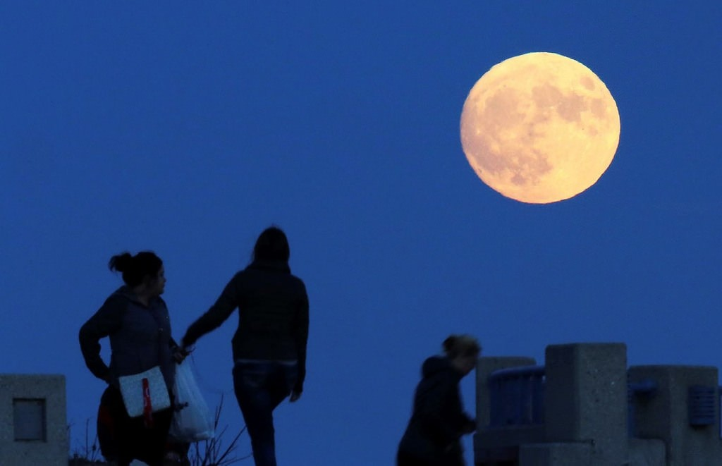 On the eve of the so-called supermoon, visitors enjoy an unobstructed view of the spectacle as it ascends over the Lake Michigan shoreline in Milwaukee, Wis., Sunday, Nov. 13, 2016. AP Photo