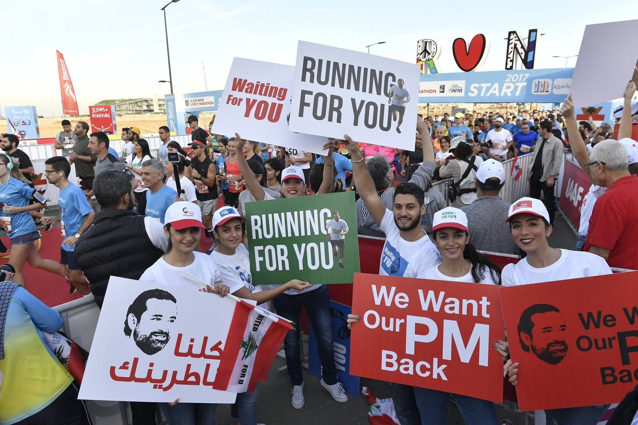 Lebanese youth hold placards demanding the return of Lebanese Prime Minister Saad Hariri from Saudi Arabia during the annual Beirut International Marathon, Beirut, Lebanon, Nov. 12, 2017. (EPA Photo)