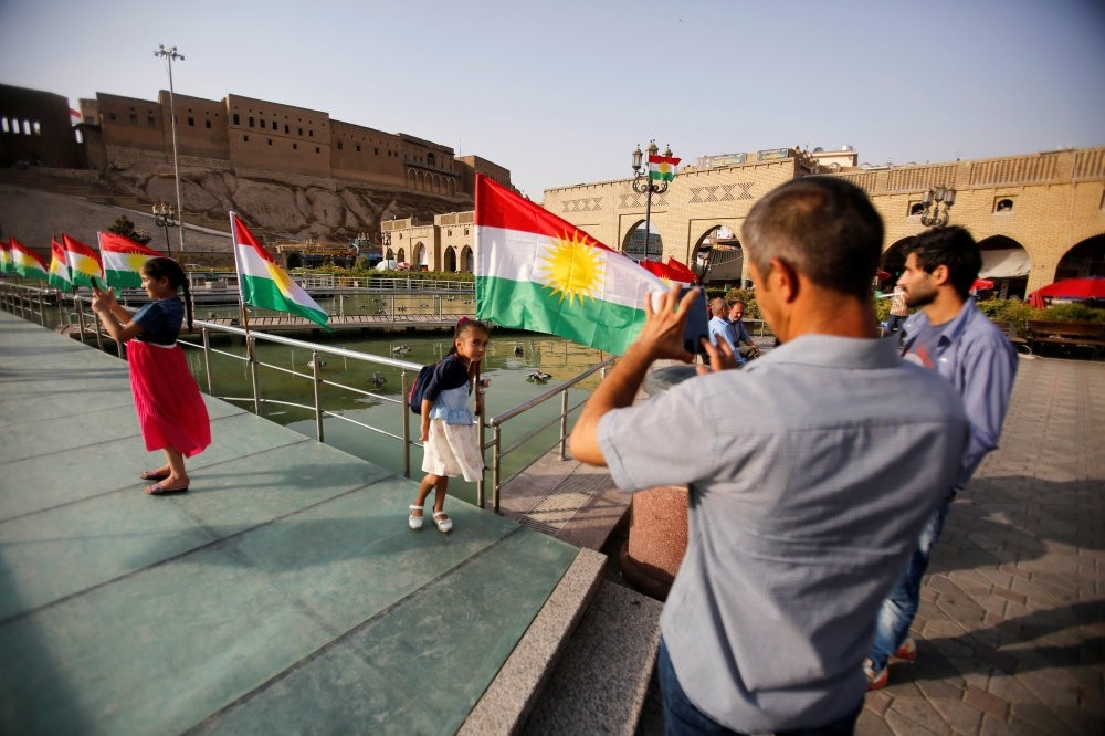 A man takes a picture of his daugther near the Kurdistan flag at the castle of Irbil, northern Iraq, July 29, 2017.