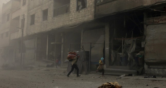 Syrians run from cover in Hamouria during regime shelling in the Eastern Ghouta suburb of Damascus, March 6.
