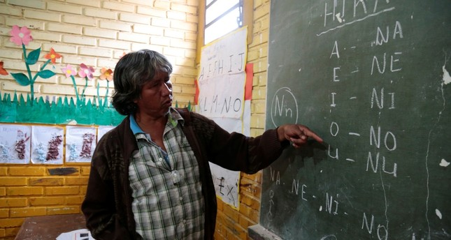 Teacher Blas Duarte shows letters in the Maka language at a school used by children of the Paraguayan ethnic group Maka, in Paraguay.