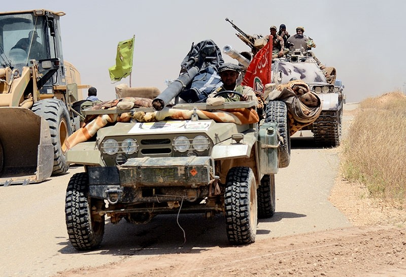 Popular Mobilization Forces (PMF) ride in military vehicles during a battle with Daesh militants, at Um Jaris village on the Iraqi border with Syria, Iraq May 29, 2017.  (Reuters Photo)