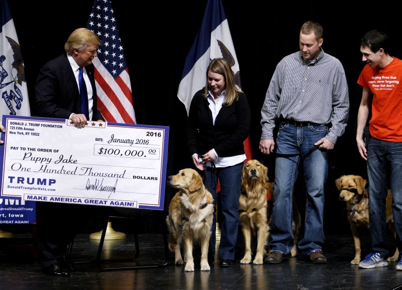 Donald Trump presents a mock check from the Trump Foundation representing $100,000 to members of the Puppy Jake Foundation, which provides military veterans with trained service dogs, in Davenport, Iowa, U.S., Jan. 30, 2016. (Reuters Photo)
