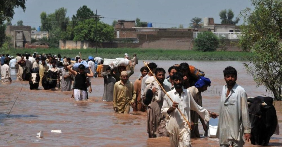 In a file picture taken on July 31, 2010, evacuating residents carry their belongings through floodwaters in the Mohib Bhanda area in Nowshera district. (AFP Photo)