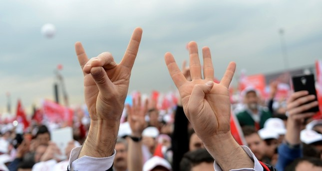 A man's hands seen making the grey wolf, left, and rabia signs during a political rally in Istanbul.