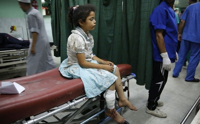 A Palestinian girl sits on a bed at a hospital in Beit Lahita in the northern Gaza Strip, July 30, 2014.