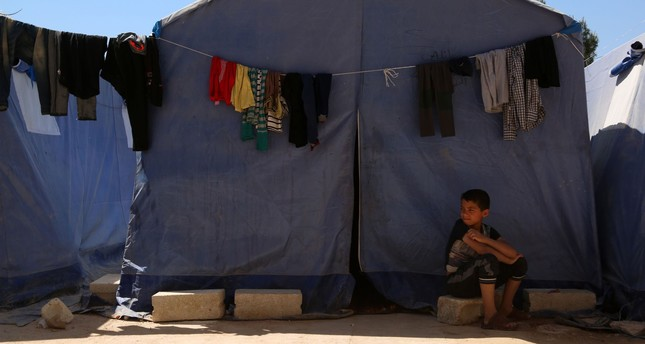 A Syrian boy, displaced from Ghouta following regime chemical weapons attacks, sits outside a tent in a make-shift camp built inside a school in Atareb, northern Syria, April 7.