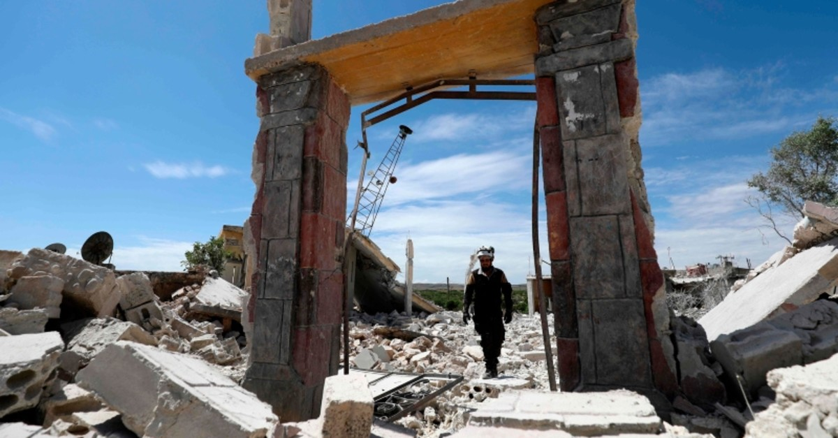 A member of the Syrian Civil Defense (White Helmets) inspects the rubble following shelling by Syrian regime forces and their allies on a the village of Maarit Sin in the countryside of the opposition-held Idlib province on May 11, 2019. (AFP Photo)