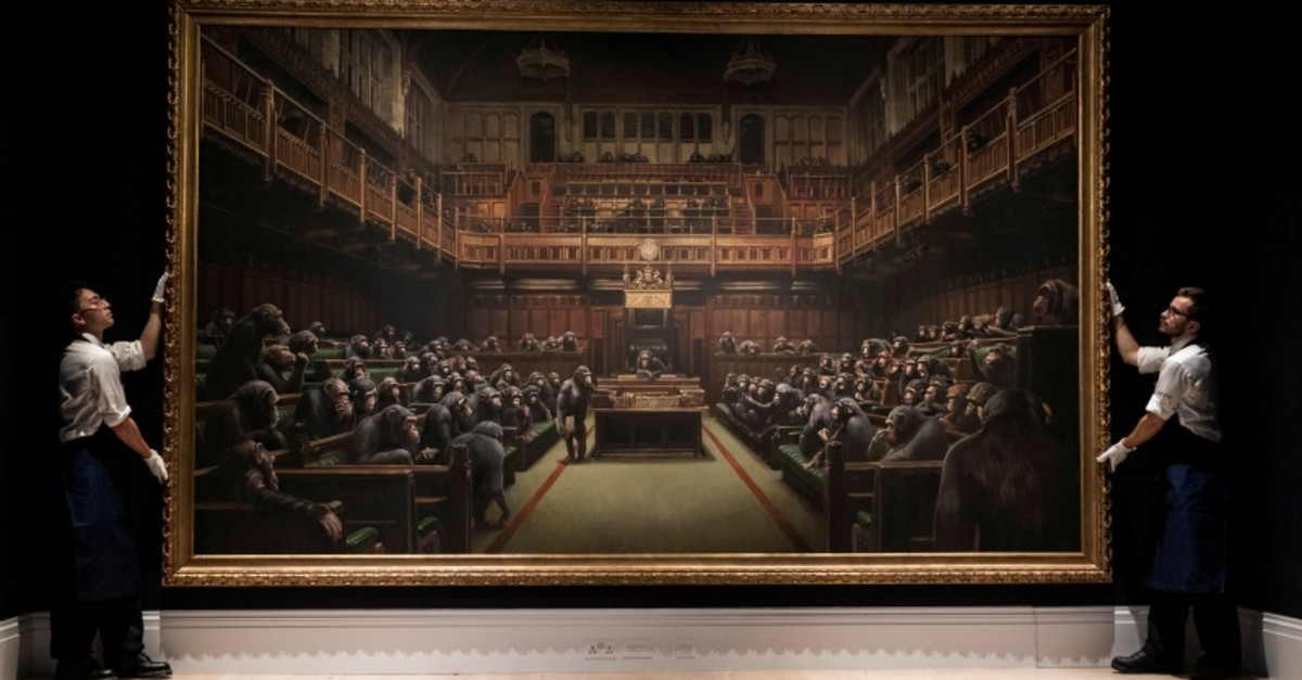 otheby's staff pose for a photograph with Banksy's 'Devolved Parliament' which has an estimated value of 1.5-2 million British pounds in a forthcoming sale in  London, Britain September 27, 2019. (Reuters Photo)