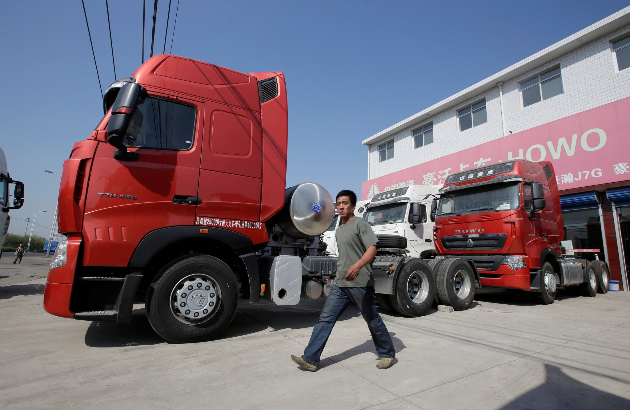 A man walks past liquefied natural gas (LNG) trucks for sale outside a heavy-duty truck shop in Yutian county, Chinau2019s Hebei province.
