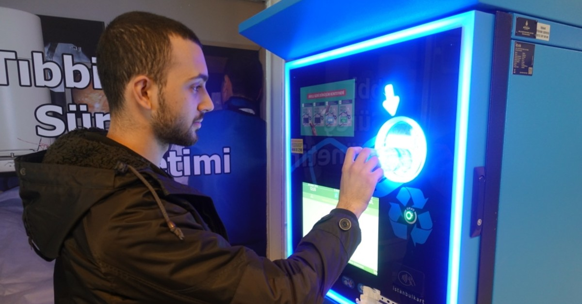 A man deposits a plastic bottle into Istanbul municipality's reverse vending machine, Feb. 28, 2019.