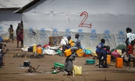 A young South Sudanese refugee girl drinks water from a plastic container at the Imvepi reception center, June 6.