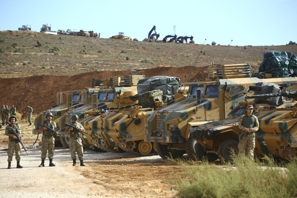 Turkish soldier and armored vehicles wait at the Syria-Turkey border in Hatay before the start of the operation.