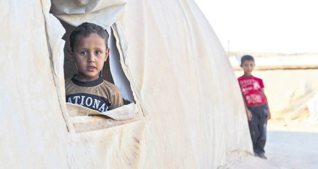 A young boy looks out from a tent in a camp for the displaced in southern Idlib, a short distance from the border with Turkey, Aug. 26.