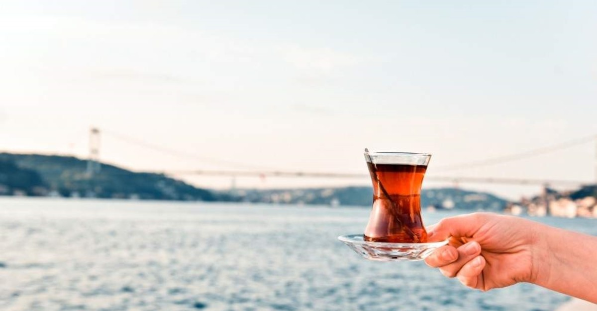 A woman holds a glass of black tea at the Bosporus, Istanbul. (iStock)
