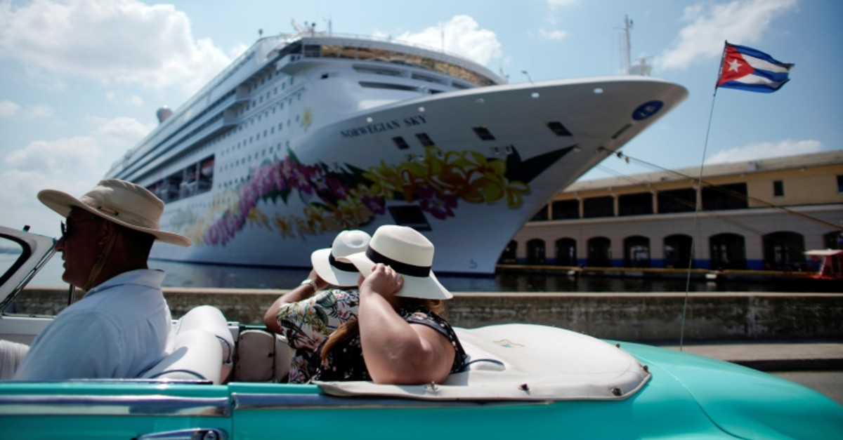 Tourists ride inside a vintage car as they pass by the Norwegian Sky cruise ship, operated by Norwegian Cruise Lines in Havana, Cuba, May 7, 2019. Picture taken May 7, 2019. (Reuters Photo)