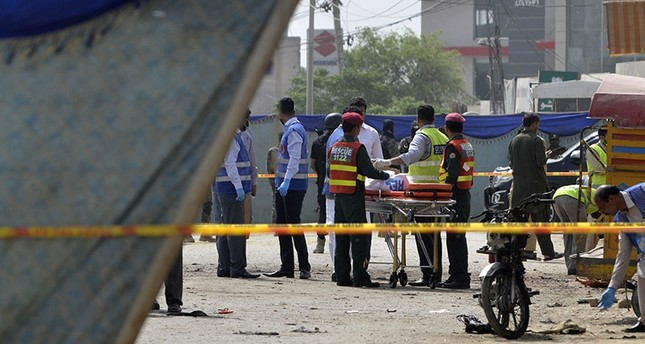 Pakistani security officials collect evidence from the scene of a suicide bomb attack on a census team in Lahore on April 5, 2017. (AFP Photo)