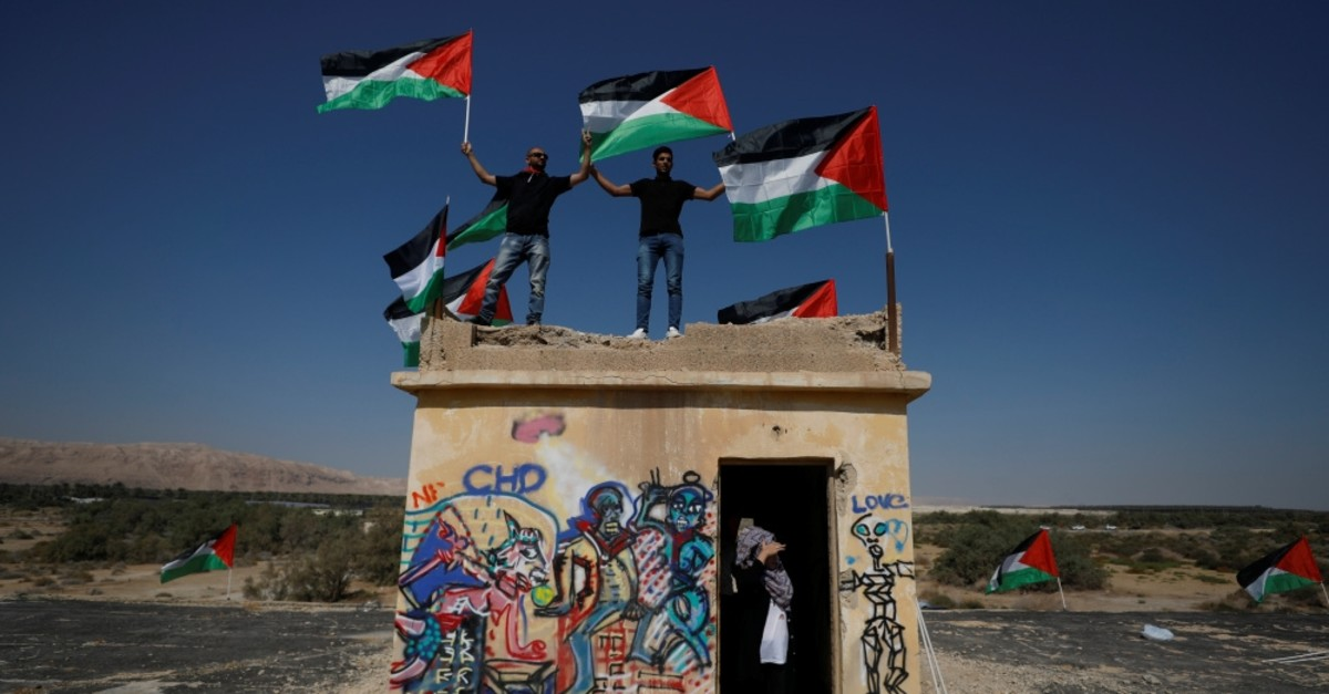 Demonstrators hold Palestinian flags during a protest against Jewish settlements, near the Dead Sea in the Israeli-occupied West Bank, Sept. 28, 2019.