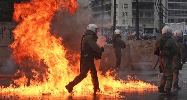 A molotov cocktail explodes next to Greek riot police during clashes after a rally in Athens, Sunday, Jan. 20, 2019. (AP Photo)