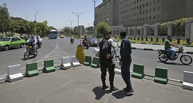 Police officers stand guard as vehicles drive past Iran's parliament building in Tehran, Iran, Thursday, May 8, 2017. (AP Photo)