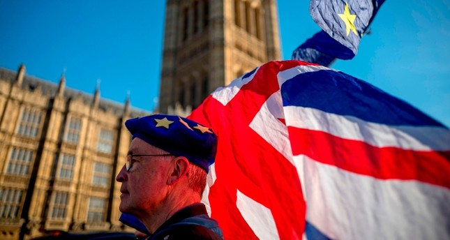 An anti-Brexit protester wearing a European Union flag cap, flies European and Union flags outside the Houses of Parliament in London on Feb. 21, 2019 (AFP Photo)